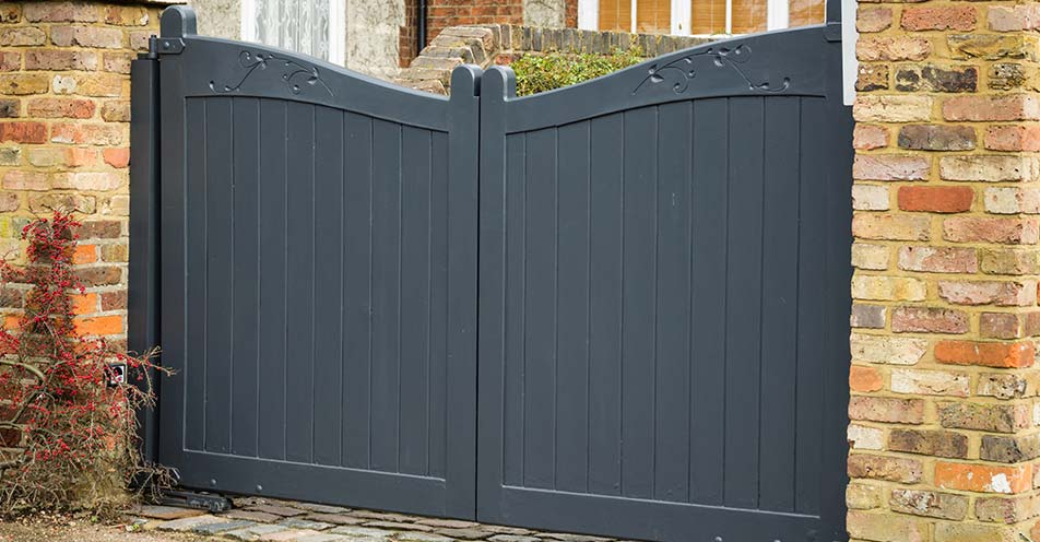 wooden gates installed between brick posts